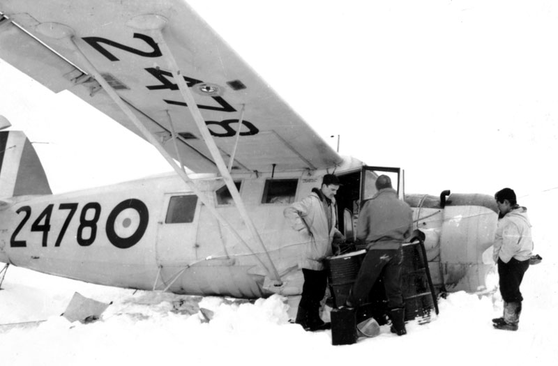 Photo: Captain McVicar inspects crashed Norseman while Inuit man looks on.